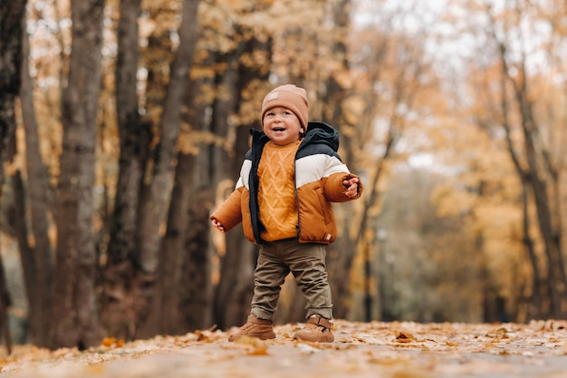 Un ragazzino sorride in un parco d'autunno. una famiglia cammina attraverso il parco naturale autunno dorato.