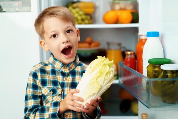 Ragazzino in piedi davanti al frigorifero aperto e scegliere il cibo