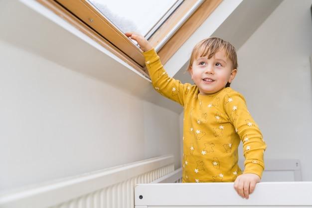 Un ragazzino in piedi nel suo letto la mattina e toccando la finestra del tetto con la sua mano.