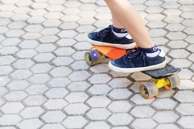Little boy in piedi su uno skateboard arancione all'aperto