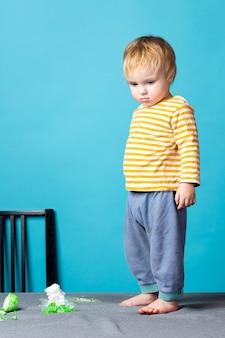 Un ragazzino è in piedi sul tavolo e sembra sconvolto perché ha rotto i cristalli. il bambino è dispettoso e arrabbiato