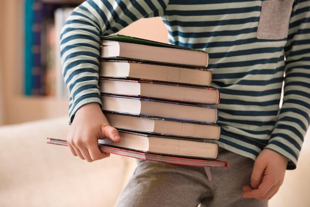 Ragazzino in una camicia a righe che tiene una pila di libri come concetto di educazione e conoscenza