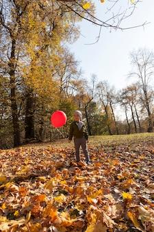 Ragazzino che passeggia nel parco con un palloncino rosso che vola alto tra gli alberi sopra la testa del bambino, divertimento per il ragazzino Foto Premium
