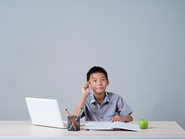 Ragazzino che studia in linea con il computer portatile. apprendimento a distanza durante la pandemia covid-19