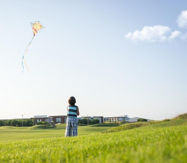 Ragazzino sulle vacanze estive divertendosi e tempo felice che pilota aquilone sulla spiaggia del mare