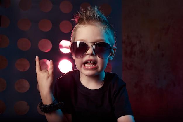 Un ragazzino in occhiali da sole mostra le sue dita