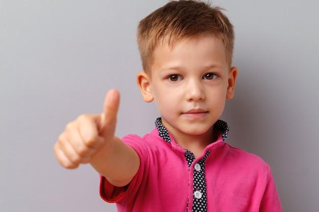 Il ragazzino in maglietta che mostra i pollici su firma sopra il fondo grigio