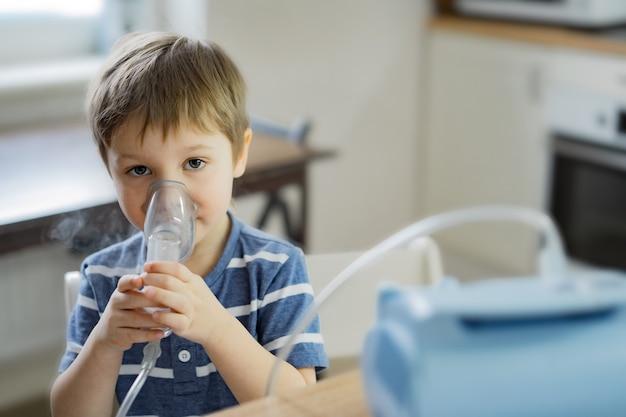 Ragazzino che fa terapia inalatoria respiratoria con nebulizzatore mentre guarda cartoni animati al telefono