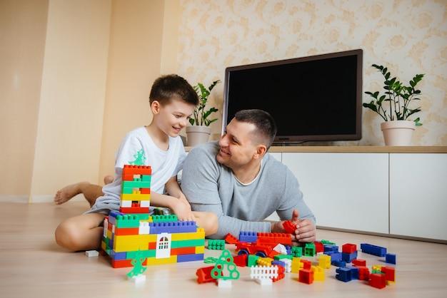 Un bambino insieme a suo padre è interpretato da un costruttore e costruisce una casa. costruzione di una casa di famiglia.