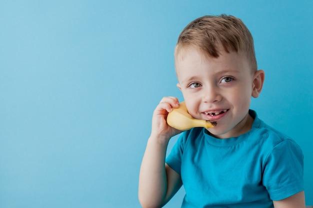 Little boy cerca di parlare per mezzo di una banana invece del telefono.