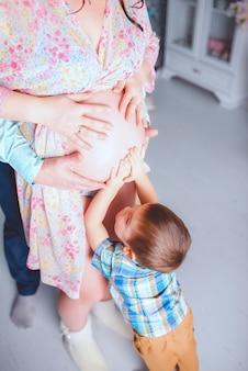 Un bambino, in attesa di sua sorella, tocca delicatamente la pancia della madre