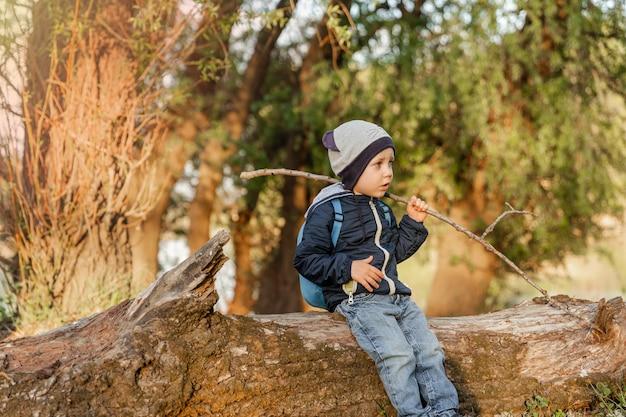 Un ragazzino che cammina in legno ragazzino che esplora la vacanza nella natura