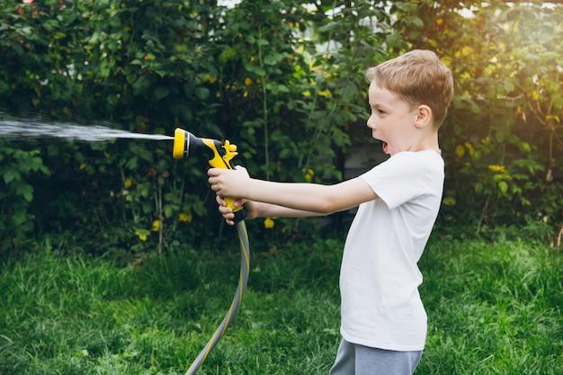 Ragazzino che innaffia il giardino con un tubo flessibile.