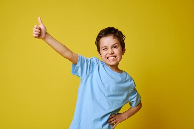 Ragazzino che indossa la maglietta estiva blu che mostra il pollice in alto su sfondo giallo mentre posa alla macchina fotografica.