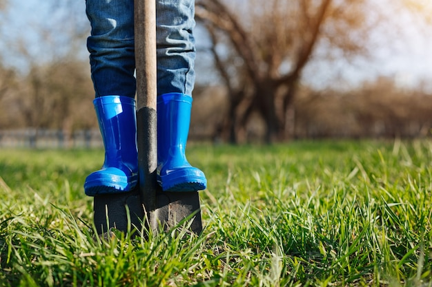 Ragazzino che indossa stivali di gomma blu luminosi che aiutano i suoi familiari scavando una vanga nel terreno