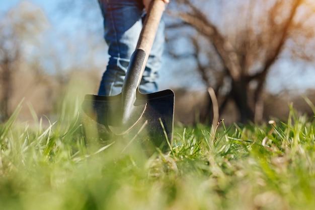 Un ragazzino che indossa jeans che aiuta la sua famiglia scavando con una vanga nel cortile