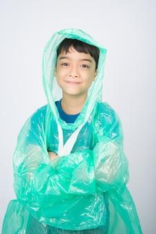 Little boy indossa un cappotto di pioggia sul muro bianco