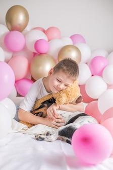 Ragazzino in palloncini bianchi con lui cane