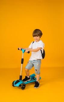 Il ragazzino in una maglietta bianca e pantaloncini di jeans cavalca uno scooter su una superficie gialla con spazio per il testo. sport di strada