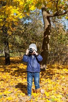 Il ragazzino con una fotocamera fotografa guardando direttamente nella fotocamera, un ritratto in primo piano del parco di autunno.