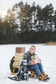 Ragazzino con scatole regalo di natale che si siede sulla slitta di legno