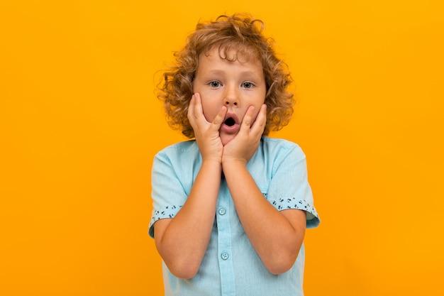Il ragazzino con capelli ricci in camicia e shorts blu è shoked isolato su giallo