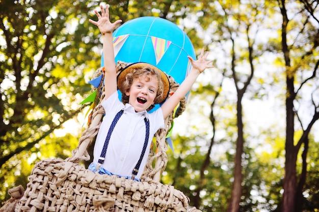 Un ragazzino con i capelli ricci con un cappello di paglia in un cesto di palloncini sorride e si gode il viaggio. infanzia, sogni, fantasie