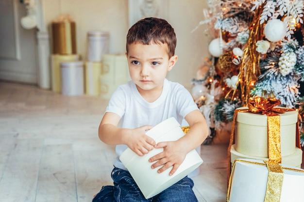 Ragazzino con confezione regalo vicino all'albero di natale alla vigilia di natale a casa. ragazzino in una stanza luminosa con decorazioni invernali. famiglia felice a casa. natale capodanno dicembre per il concetto di celebrazione.