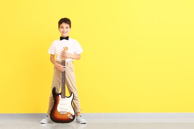 Ragazzino con la chitarra vicino alla superficie del colore