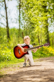 Ragazzino con la chitarra nel parco estivo