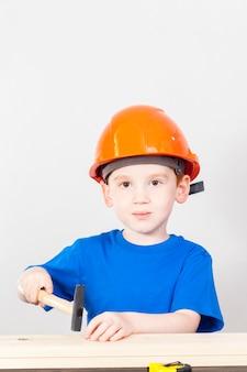 Ragazzino con un martello e altri strumenti di costruzione durante le lezioni di educazione al lavoro
