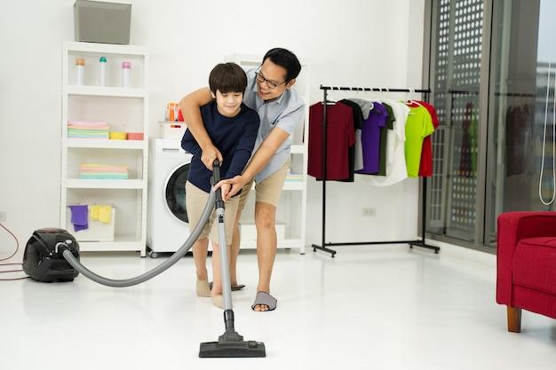 Il ragazzino con suo padre usa l'aspirapolvere nella stanza. padre e figlio che fanno le pulizie in casa.
