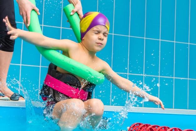 Un bambino con un giubbotto di salvataggio sul petto impara a nuotare in una piscina coperta.