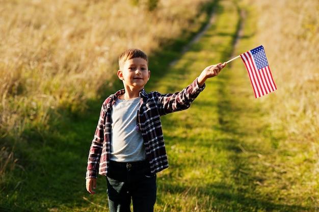 Ragazzino con bandiera usa all'aperto. l'america festeggia.
