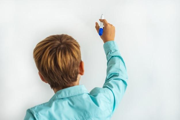 Il ragazzino che scrive sul muro bianco