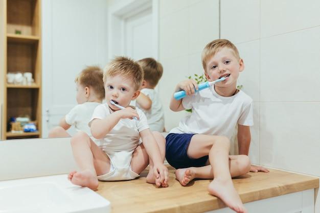 Ragazzini bambini che lavano i denti in bagno, due fratelli