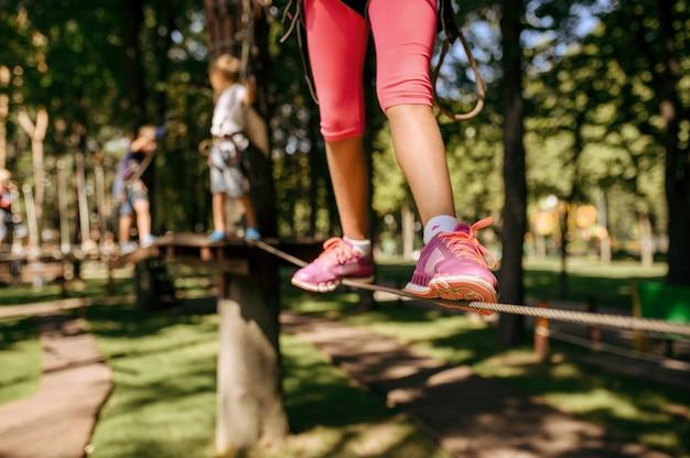La piccola ragazza coraggiosa si arrampica nel parco avventura