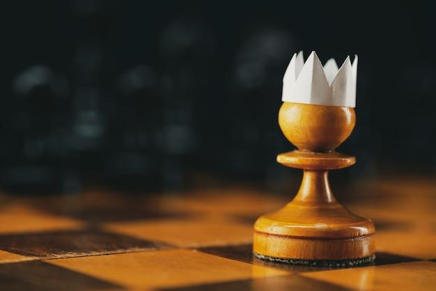 Piccolo pedone coraggioso che indossa la tuta di carta artificiale sulla scacchiera con figure, concetto di leadership di imprenditore aziendale.