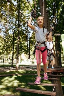 Il fratellino e la sorella si arrampicano nel parco avventura. bambini che si arrampicano sul ponte sospeso, avventura sportiva estrema in vacanza, intrattenimento all'aperto