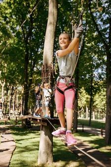 Il fratellino e la sorella si arrampicano nel parco avventura. bambini che si arrampicano sul ponte sospeso, avventura sportiva estrema