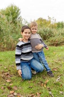Piccoli fratelli che abbracciano e che ridono. amore, fiducia e tenerezza