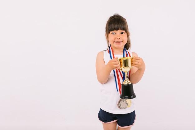 Piccola ragazza dai capelli castani con medaglie di campioni sportivi, che tiene un trofeo con entrambe le mani. sport e concetto di vittoria