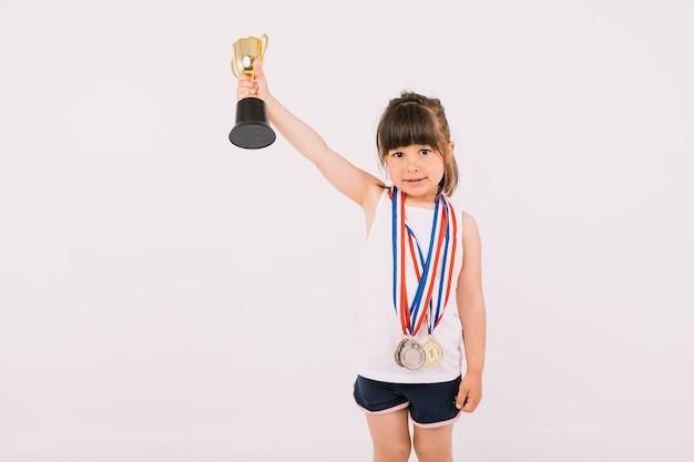 Piccola ragazza dai capelli castani con medaglie di campioni sportivi, che solleva un trofeo con una mano. sport e concetto di vittoria