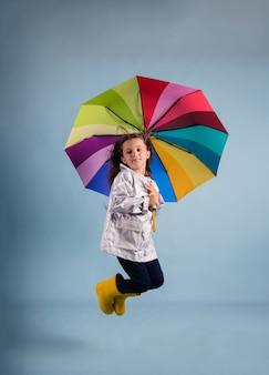 Una piccola ragazza bruna con un impermeabile e stivali di gomma salta sotto un ombrello multicolore su uno sfondo blu con un posto per il testo