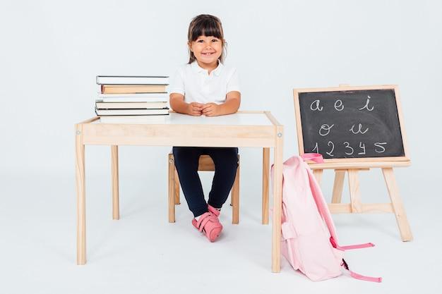 Piccola ragazza bruna a scuola, seduto su sfondo bianco