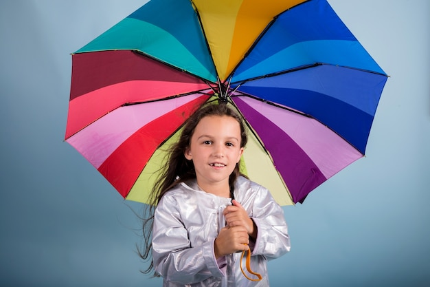 Piccola ragazza bruna con un ombrello multicolore su sfondo blu con una copia dello spazio