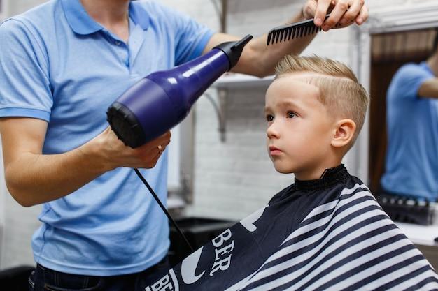 Piccolo ragazzo caucasico in barberia ragazzo biondo su un taglio di capelli parrucchiere in processo su background