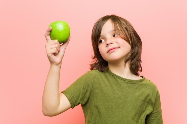Piccolo ragazzo caucasico che tiene una mela