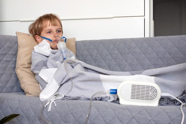 Piccolo ragazzo caucasico che fa l'inalazione con il nebulizzatore a casa.