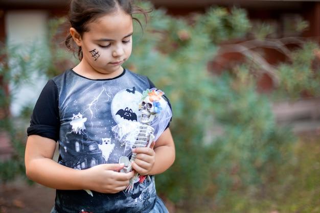 Piccolo bambino caucasico travestito da strega con scheletro giocattolo tra le braccia. lei è all'aperto. spazio per il testo.